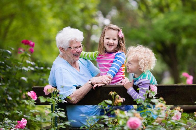 Großmutter sitzt lachend mit Enkelkindern im Park