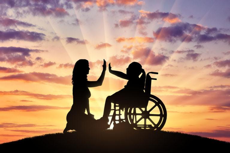 Glückliches behindertes Mädchen im Rollstuhl macht High Five mit ihrer Mutter