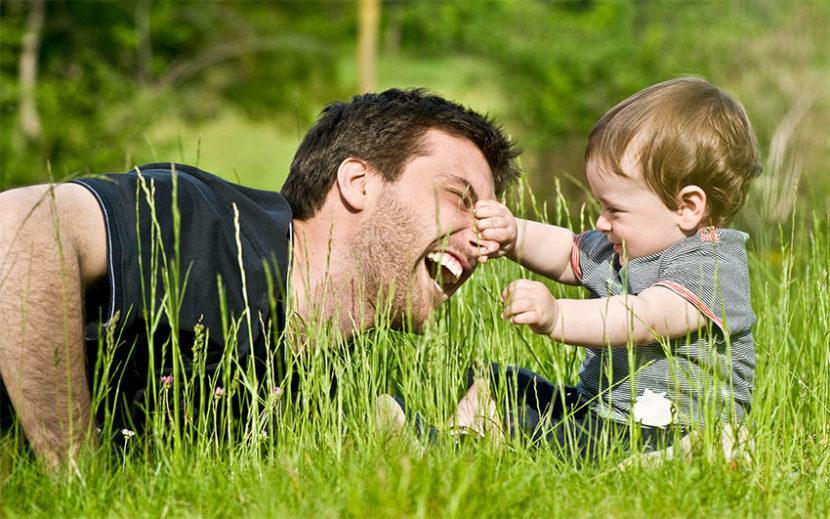 Papa spielt mit Kind auf Wiese