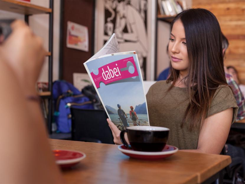 Junge Frau liest das Magazin 21/22 in einem Cafe