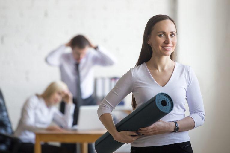 Geschäftsfrau auf dem Weg von der Arbeit zum Sport mit Yogamatte in der Hand