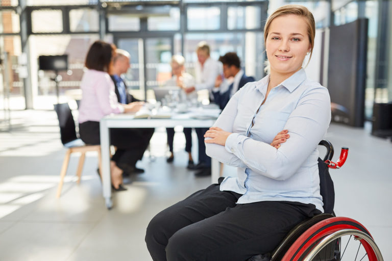 Selbstbewusste Geschäftsfrau im Rollstuhl im Meeting