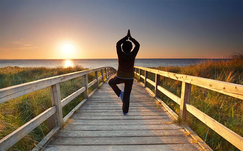 Yoga am Steg zum Meer bei Sonnenuntergang